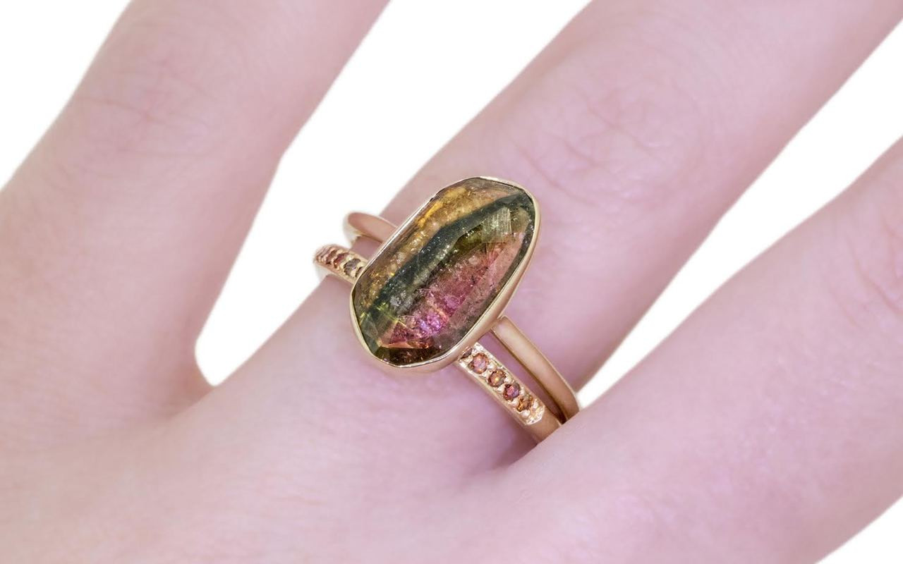 2.89 carat watermelon tourmaline set in 14k yellow gold 1/2 round band. with Wedding Band with 16 rubies in 14k yellow gold on a hand