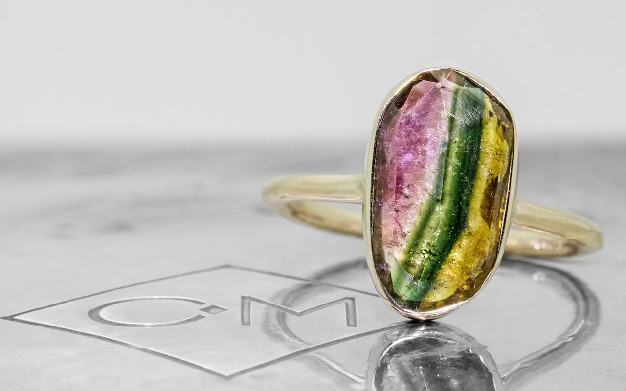 2.89 carat watermelon tourmaline set in 14k yellow gold 1/2 round band. front view on metal background with