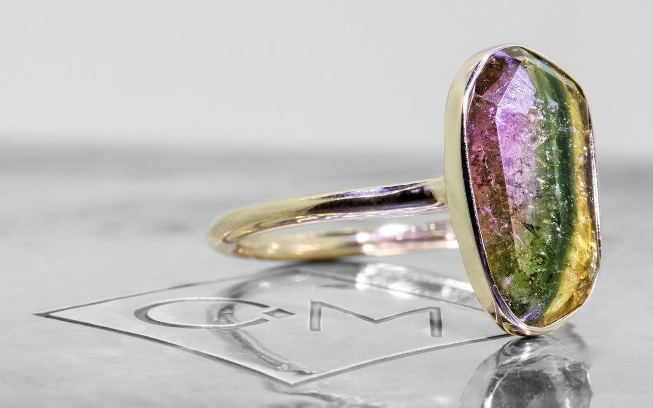 2.89 carat watermelon tourmaline set in 14k yellow gold 1/2 round band. 3/4 view on metal background with Chinchar/Maloney logo