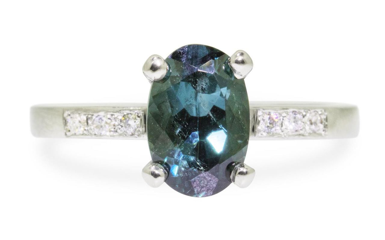 1.70 carat oval, faceted cut deep blue/green tourmaline with six 1.2mm brilliant white diamonds set in 14k white gold flat band. Front view on white background