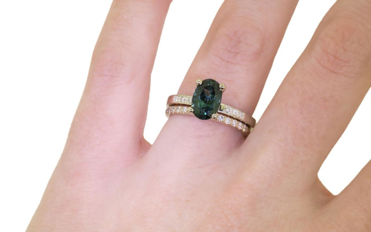 1.70 carat oval, faceted cut deep blue/green tourmaline with six 1.2mm brilliant white diamonds set in 14k white gold flat band. With Wedding Band with 16 brilliant white diamonds set in 14k white gold on a hand