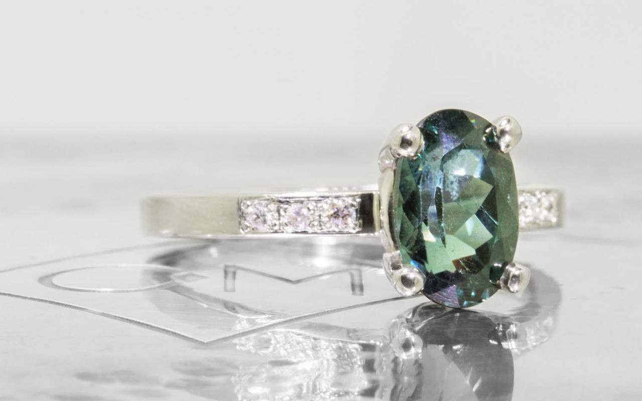 1.70 carat oval, faceted cut deep blue/green tourmaline with six 1.2mm brilliant white diamonds set in 14k white gold flat band. 3/4 view on metal background with Chinchar/Maloney logo