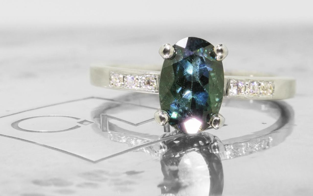 1.70 carat oval, faceted cut deep blue/green tourmaline with six 1.2mm brilliant white diamonds set in 14k white gold flat band. Front view on metal background with Chinchar/Maloney logo