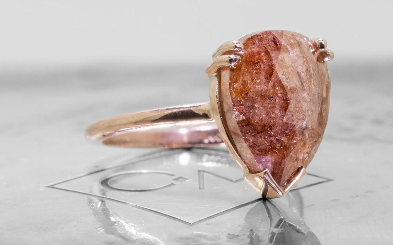 7.21 carat pear, rose cut natural rich cognac prong set diamond ring set in 14k rose gold 1/2 round band. 3/4 view on metal background with Chinchar/Maloney logo
