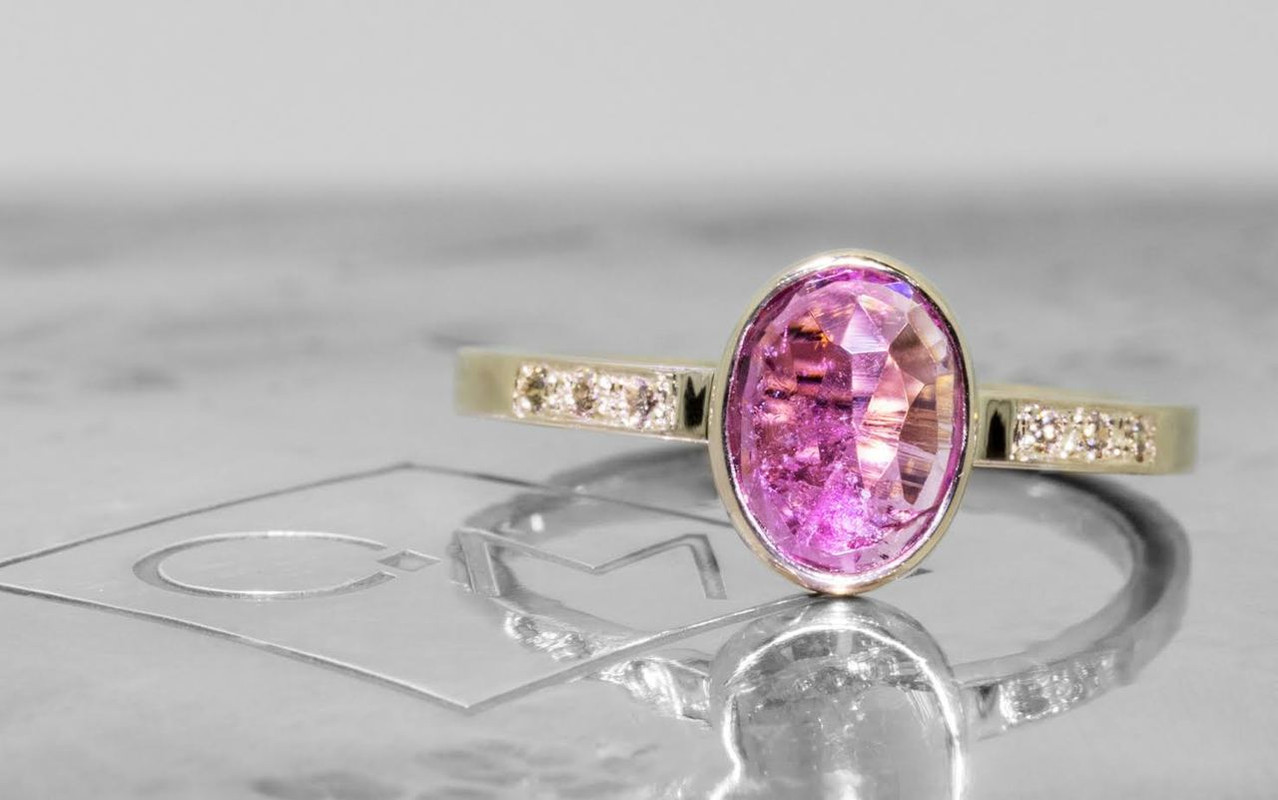 1.12 carat pink tourmaline with six 1.2mm champagne diamonds set in band. Set in 14k yellow gold. front view on metal background with Chinchar/Maloney logo.