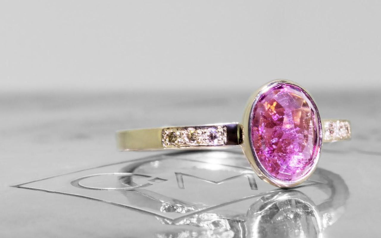 1.12 carat pink tourmaline with six 1.2mm champagne diamonds set in band. Set in 14k yellow gold. 3/4 view on metal background with Chinchar/Maloney logo