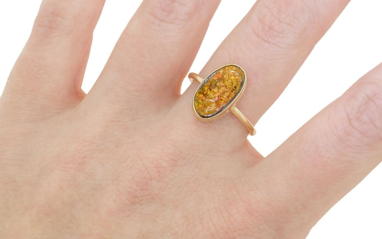 2.80 carat boulder opal in 14k yellow gold  half round band on a hand