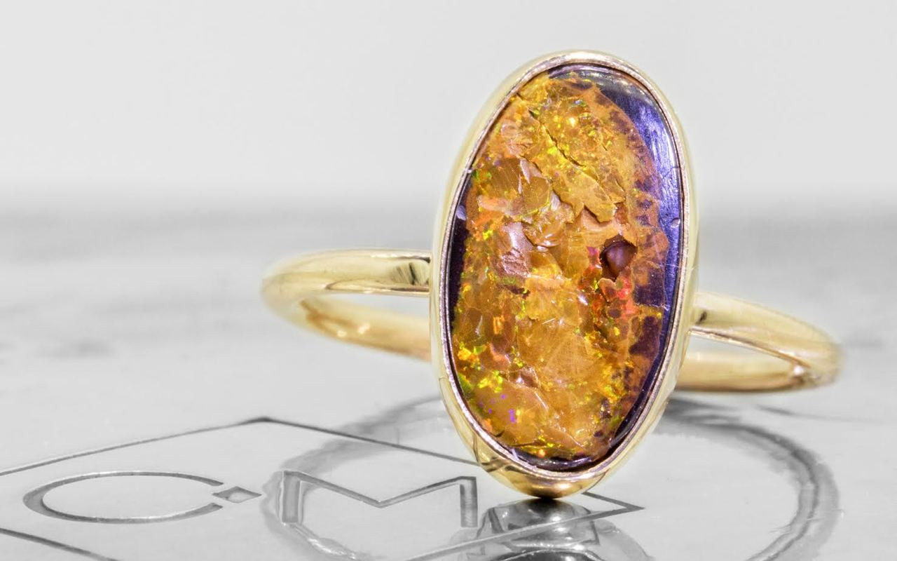 2.80 carat boulder opal in 14k yellow gold half round band front view on metal background with Chinchar/Maloney logo