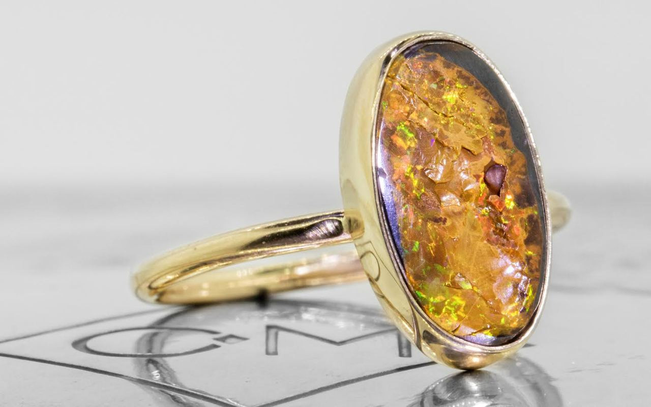 2.80 carat boulder opal in 14k yellow gold half round band 3/4 view on metal background with Chinchar/Maloney logo