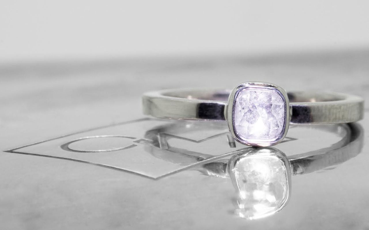 .50 carat  cushion, rose cut icy white bezel set diamond ring set in 14k white gold flat band.  Front view on metal background with Chinchar/Maloney logo