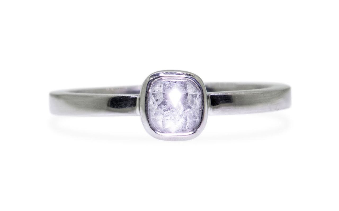 .50 carat  cushion, rose cut icy white bezel set diamond ring set in 14k white gold flat band. Front view on white background