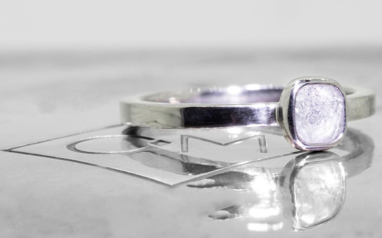 .50 carat  cushion, rose cut icy white bezel set diamond ring set in 14k white gold flat band. 3/4 view on metal background with Chinchar/Maloney logo
