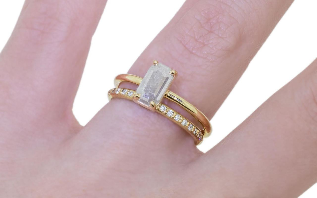 .58 carat fancy-cut gray prong set diamond ring set in 14k yellow gold 1/2 round band. With Wedding Band with 16 white brilliant diamonds set in 14k yellow gold 1/2 round band on a hand