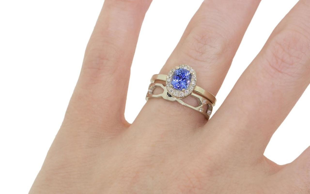 Wedding band in 14k white gold with small brilliant  blue sapphires bead set into the band.  Front view of a sapphire set in a rounded octagon section of the band.  On each side of this section are open-work sections.  Art Deco style.  Modeled on a hand and stacked with a sapphire engagement ring.