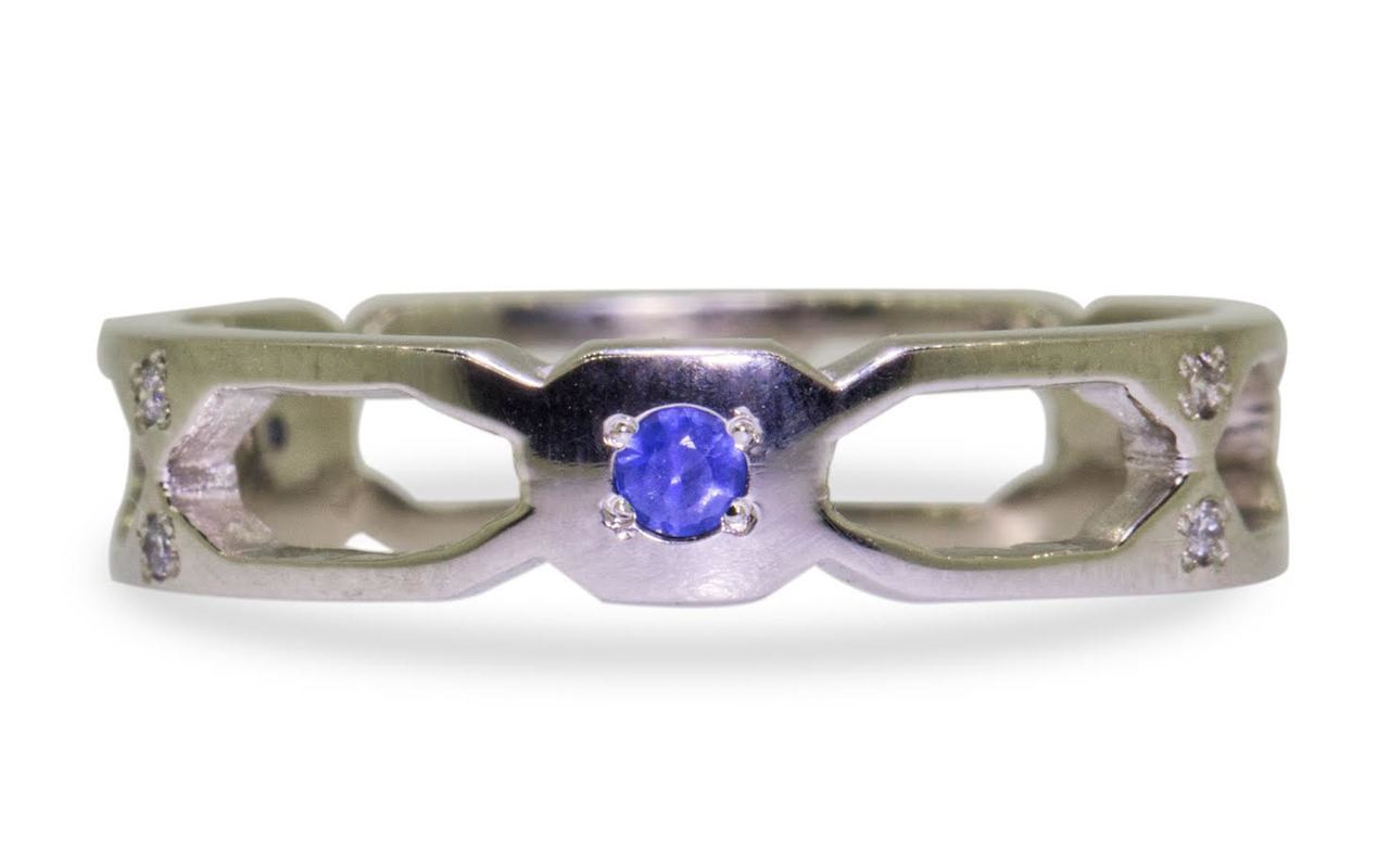Wedding band in 14k white gold with small brilliant  blue sapphires bead set into the band.  Front view of a sapphire set in a rounded octagon section of the band.  On each side of this section are open-work sections.  Art Deco style.  On white background.