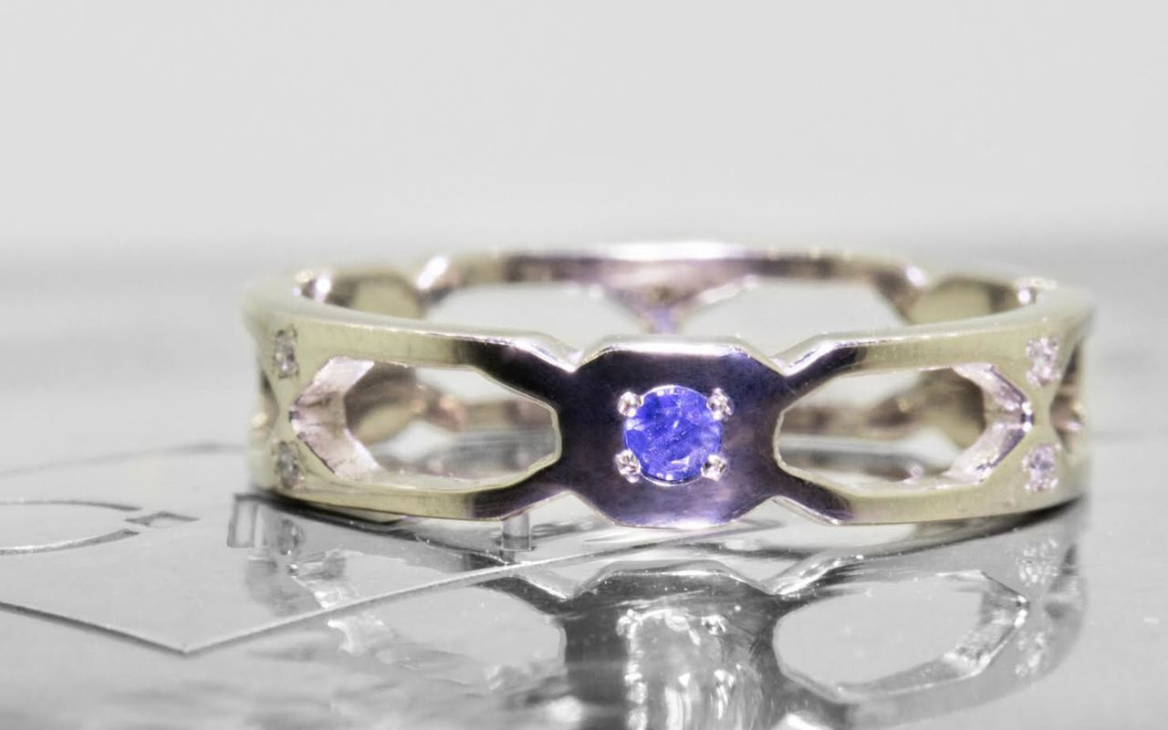 Wedding band in 14k white gold with small brilliant  blue sapphires bead set into the band.  Front view of a sapphire set in a rounded octagon section of the band.  On each side of this section are open-work sections.  Art Deco style.  On metal background with Chinchar/Maloney logo.