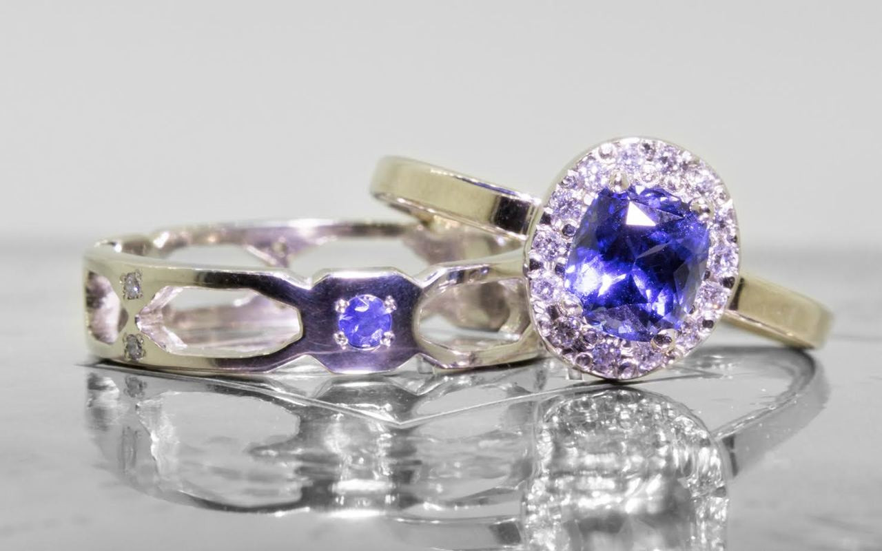 Wedding band in 14k white gold with small brilliant  blue sapphires bead set into the band.  Front view of a sapphire set in a rounded octagon section of the band.  On each side of this section are open-work sections.  Art Deco style.  With sapphire engagement ring stacked on top.  On metal background with Chinchar/Maloney logo.