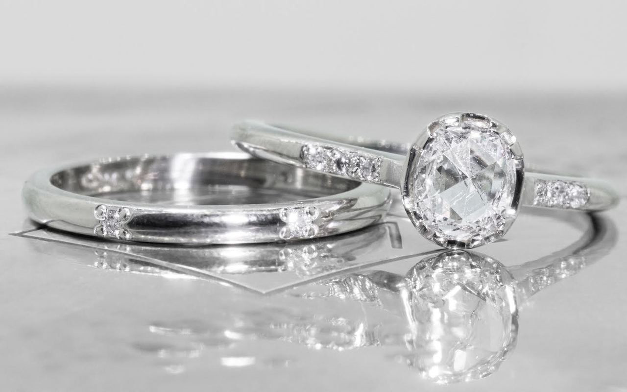 14k white gold  wedding band with 6 brilliant white pave diamonds modeled on hand on metal background with Chinchar/Maloney logo with diamond ring