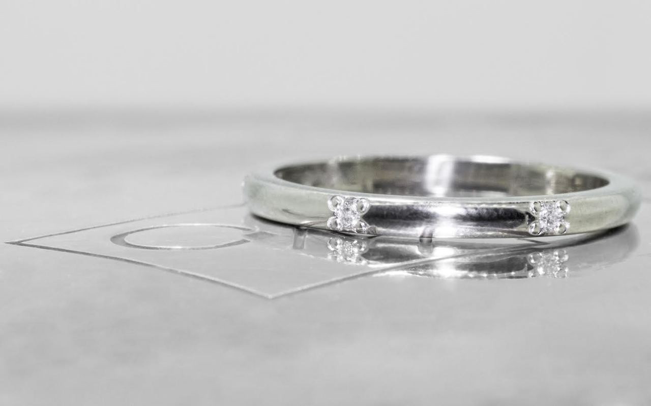 14k white gold wedding band with 6  brilliant white pave diamonds in band on metal background with Chinchar/Maloney logo