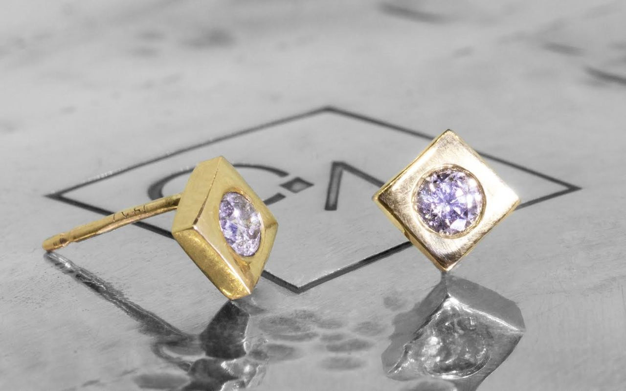 Stud earrings in yellow gold with 3mm brilliant gray diamonds set in each stud.  Studs are square-diamond shaped.  Front view of one earring and side view of the other on metal background with Chinchar/Maloney logo.