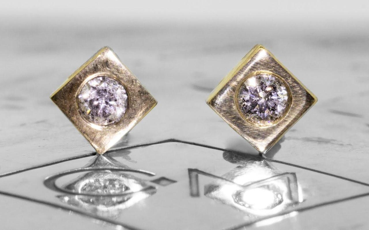 Stud earrings in yellow gold with 3mm brilliant gray diamonds set in each stud.  Studs are square-diamond shaped.  Front view on metal background with Chinchar/Maloney logo.