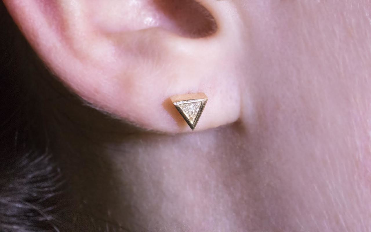3mm trillion, white diamonds set in 14k yellow gold stud earrings.  Modeled on ear.