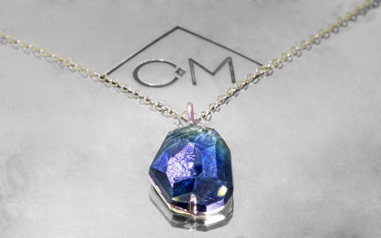 6.45 hand-cut blue green sapphire necklace set in 14k white gold with 14k white gold chain side view on metal background with Chinchar/Maloney logo
