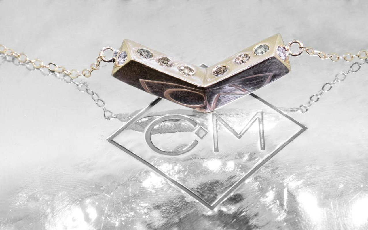 Pyramid shaped chevron pendant in 14k yellow gold on 14k yellow gold chain.  Brown, champagne, gray diamonds are set into the pendant on the top of the pendant.  On metal background with Chinchar/Maloney logo.
