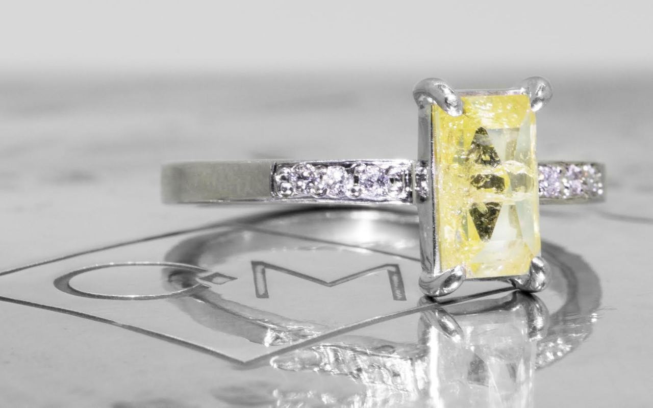 .92 carat fancy-cut sunny and vibrant yellow prong set diamond ring with six 1.2mm brilliant white diamonds set in 14k white gold flat band. 3/4 view on metal background with Chinchar/Maloney logo