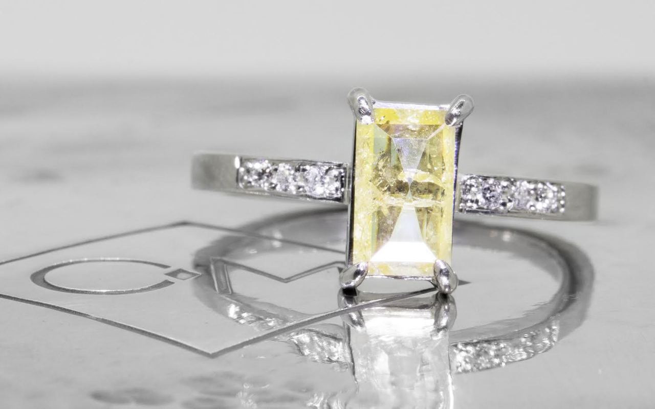 .92 carat fancy-cut sunny and vibrant yellow prong set diamond ring with six 1.2mm brilliant white diamonds set in 14k white gold flat band. Front view on metal background with Chinchar/Maloney logo
