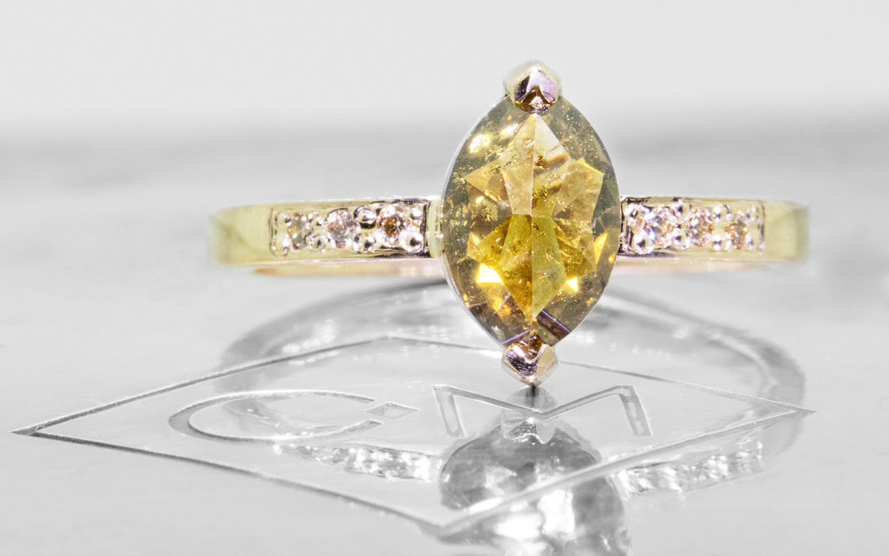 1.40 carat marquise, faceted-cut amber cognac prong set diamond ring set in 14k yellow gold with six 1.2mm brilliant champagne diamonds set in flat band.  Front view on metal background with Chinchar/Maloney logo