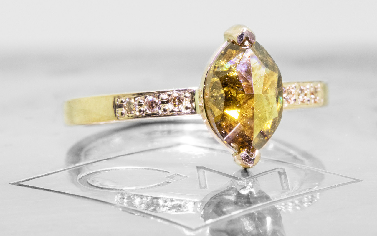1.40 carat marquise, faceted-cut amber cognac prong set diamond ring set in 14k yellow gold with six 1.2mm brilliant champagne diamonds set in flat band. 3/4 view on metal background with Chinchar/Maloney logo