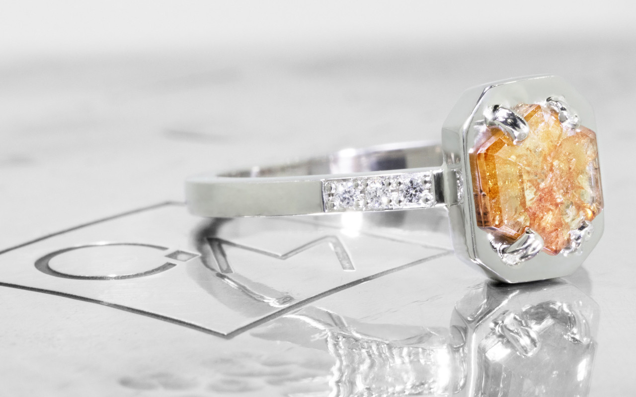 AIRA .77 carat hexagon rose cut peach champagne diamond prong set in 14k white gold geometric octangular setting. 1.2mm brilliant white diamonds set in 14k white gold band. New Classic Collection. On metal background with Chinchar/Maloney logo. Side view.