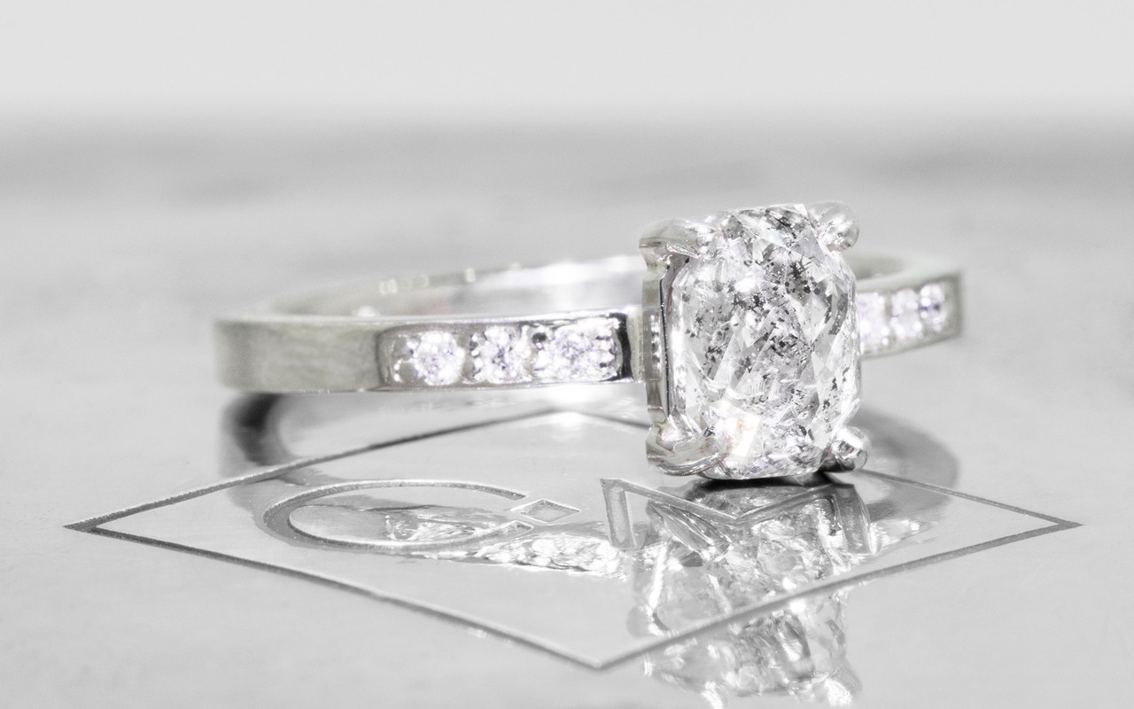 1.12 carat oval, rose cut translucent salt and pepper prong set diamond ring with six 1.2mm brilliant white diamonds set in band set in 14k white gold flat band. 3/4 view on metal background with Chinchar/Maloney logo