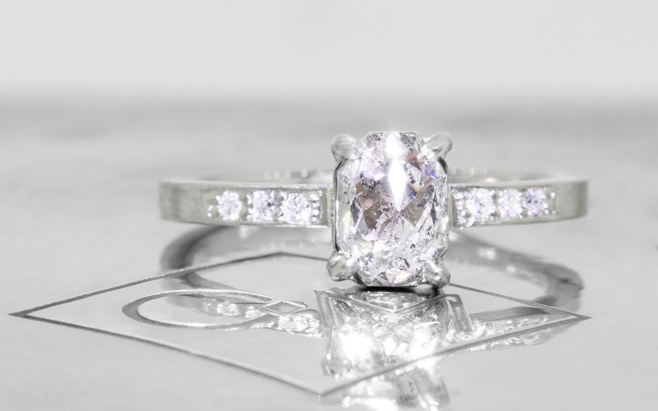 1.12 carat oval, rose cut translucent salt and pepper prong set diamond ring with six 1.2mm brilliant white diamonds set in band set in 14k white gold flat band. Front view on metal background with Chinchar/Maloney logo