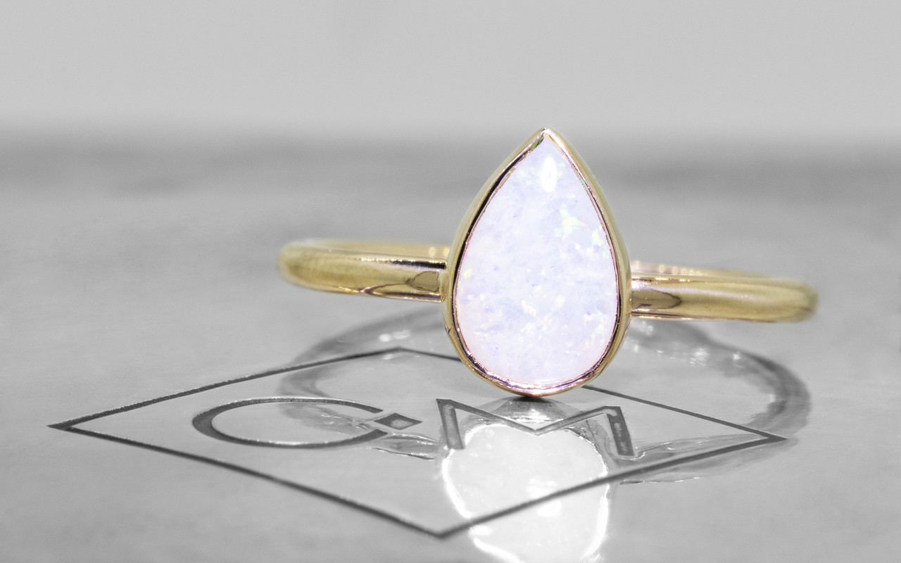 .65 carat pear white opal in 14k yellow gold half round band front view on metal background with Chinchar/Maloney logo