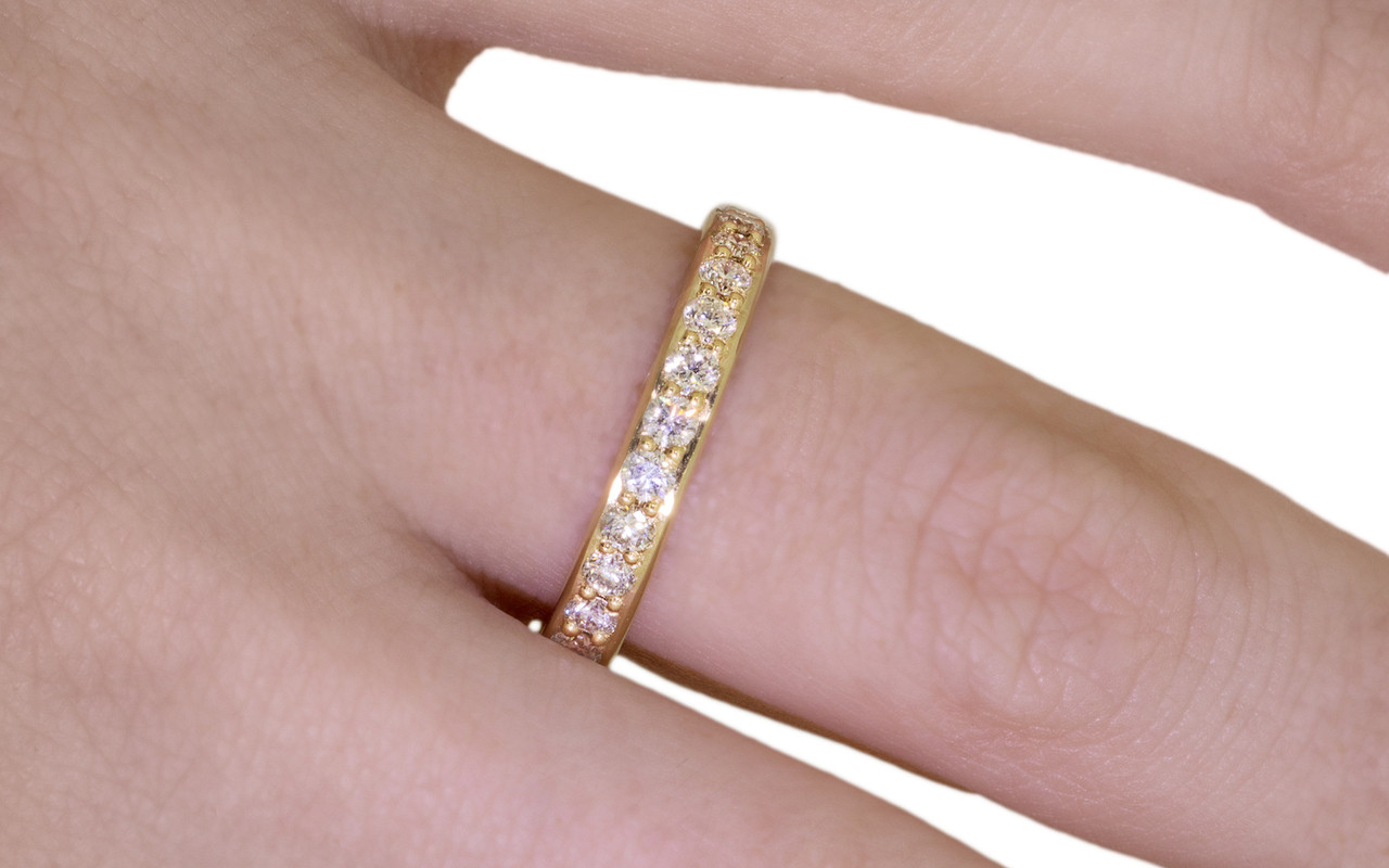 14k yellow gold wedding band with 16 brilliant champagne pave diamonds half way around band. Modeled on hand.