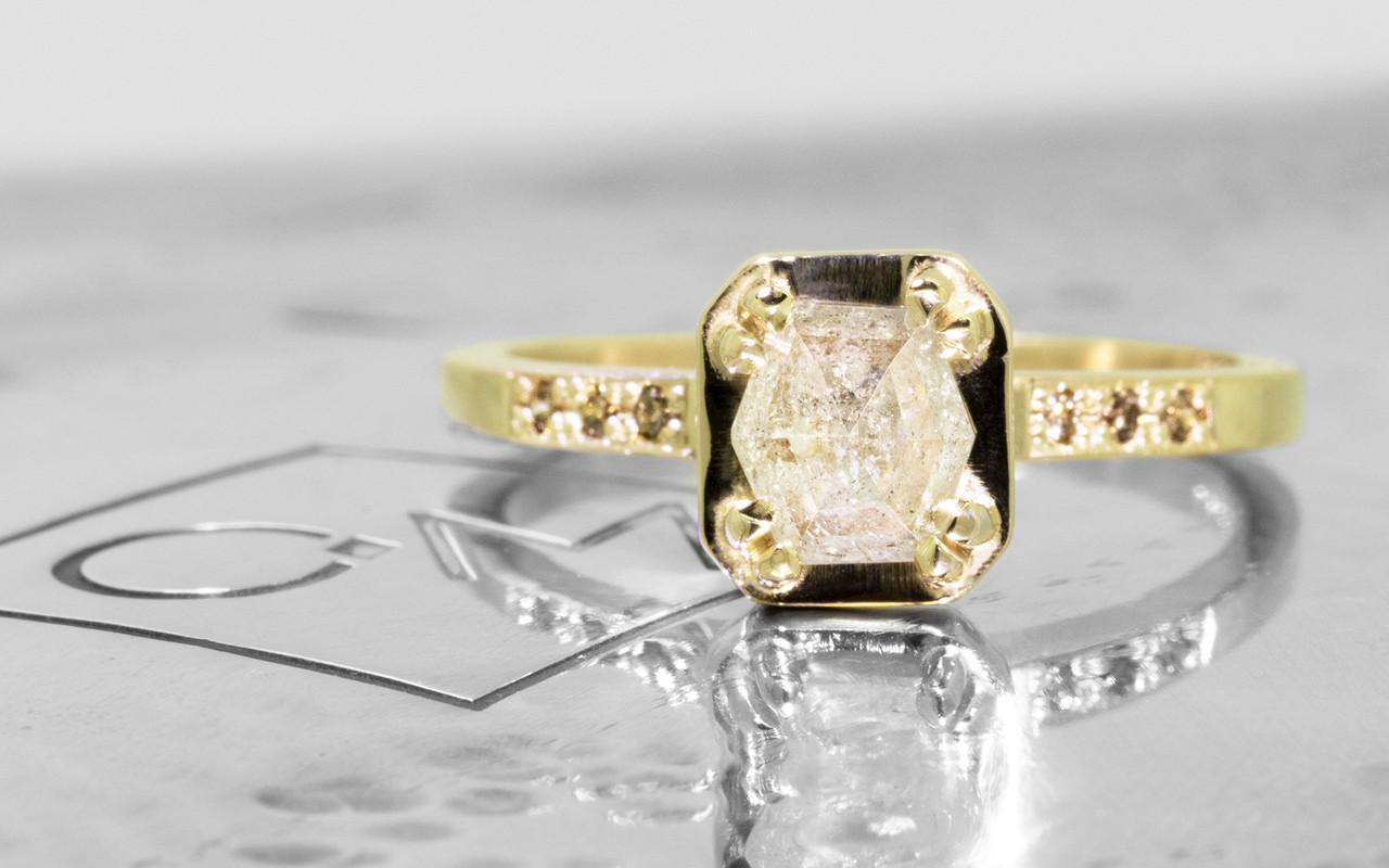 AIRA .76 carat hexagon rose cut light grayish diamond prong set in 14k yellow gold geometric octangular setting. Six 1.2mm brilliant champagne pave diamonds set in 14k yellow gold band. New Classic Collection. On metal background with Chinchar/Maloney logo.