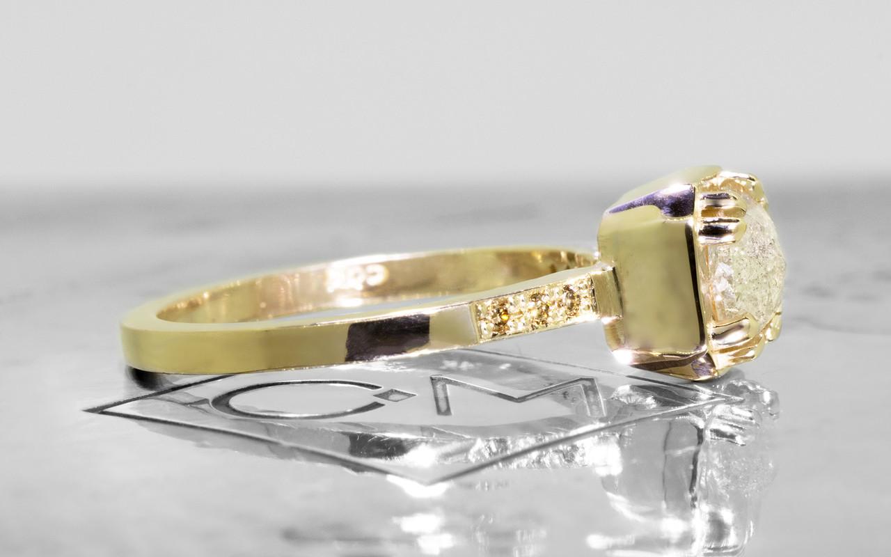 AIRA .76 carat hexagon rose cut light grayish diamond prong set in 14k yellow gold geometric octangular setting. Six 1.2mm brilliant champagne pave diamonds set in 14k yellow gold band. New Classic Collection. On metal background with Chinchar/Maloney logo. Side view.