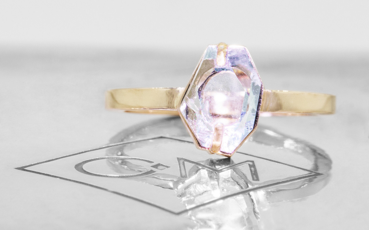 1.37 carat hand-cut aquamarine 2mm flat band front view on metal background with Chinchar/Maloney logo.  The ring is 14k yellow gold.