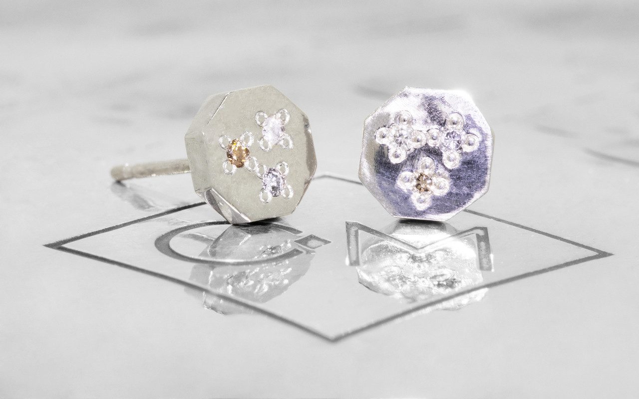 Askja 14k white gold hexagon stud earrings with white, gray and champagne pave diamonds set in surface. On metal background with Chinchar/Maloney logo