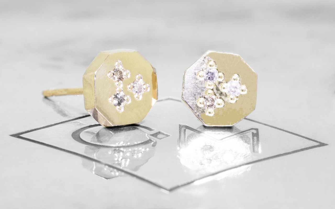 Askja 14k yellow gold hexagon stud earrings. White, gray and champagne pave diamonds set in surface.  On metal background with Chinchar/Maloney logo.