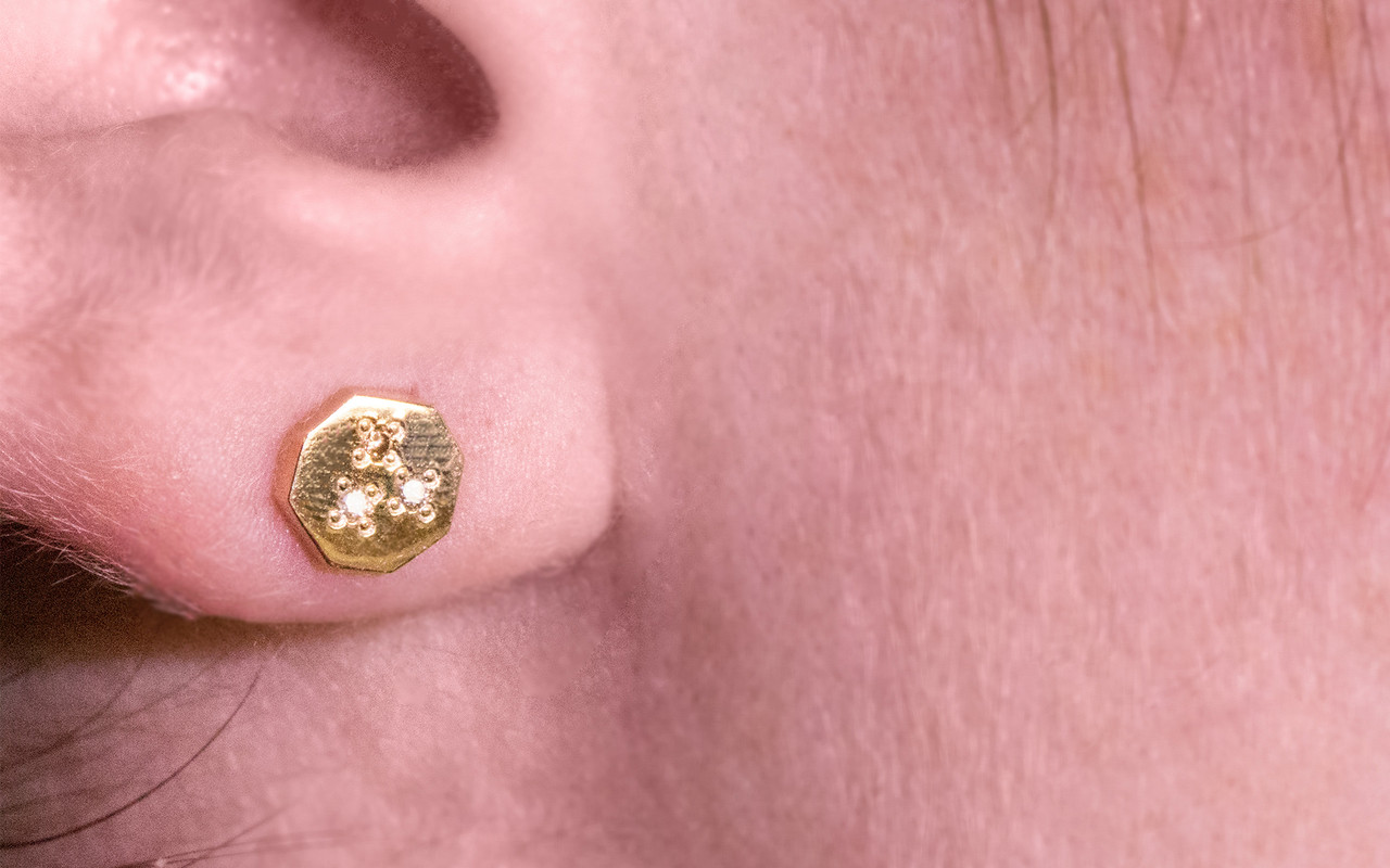 Askja 14k yellow gold hexagon stud earrings. White, gray and champagne pave diamonds set in surface. Modeled on ear.