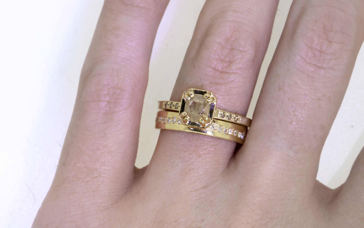 AIRA .48 carat  oval rose cut light champagne diamond prong set in 14k yellow gold geometric octangular setting. 1.2mm brilliant champagne diamonds set in 14k yellow gold band. New Classic Collection. Modeled on hand with 14k gold eternity wedding band.