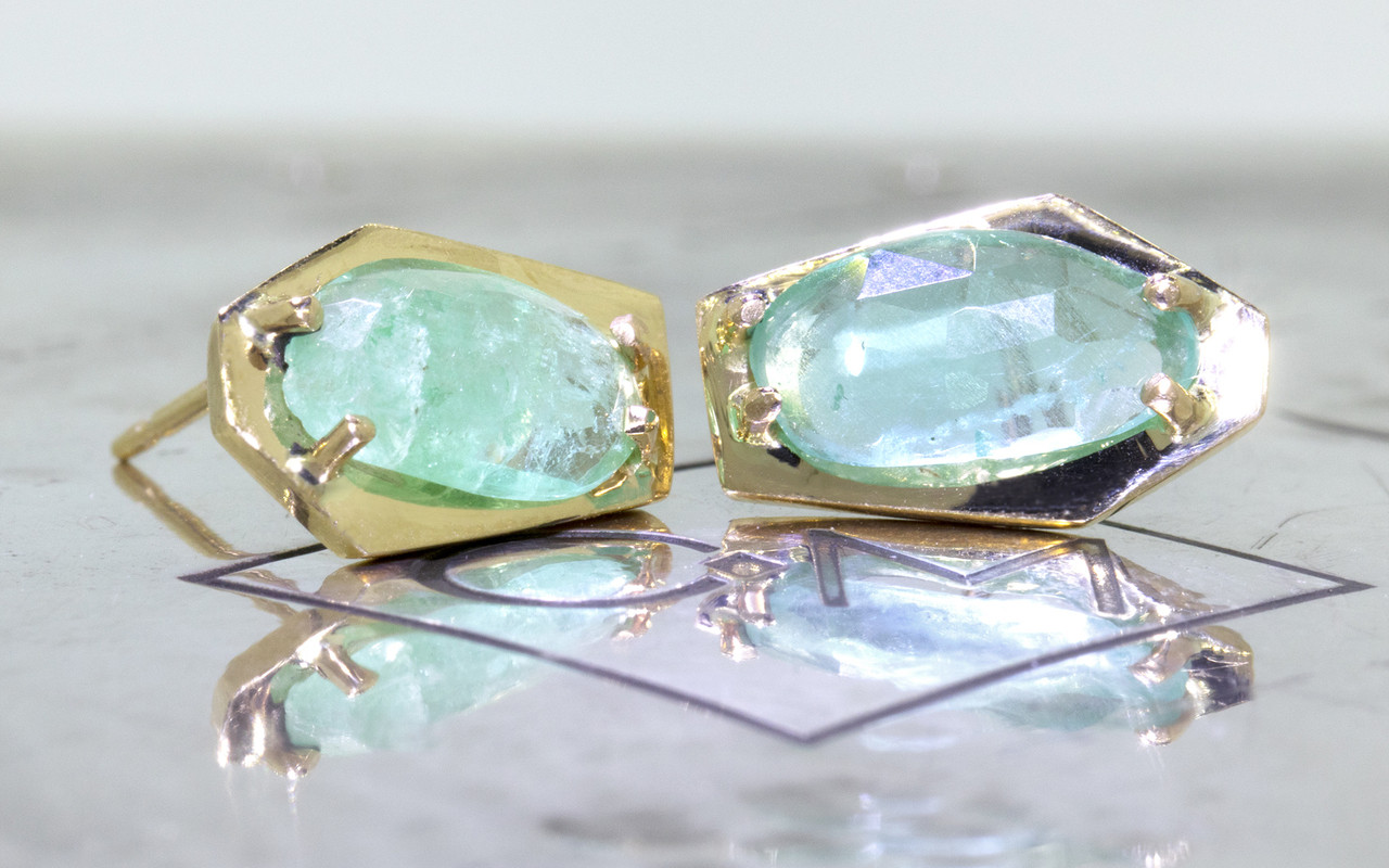 New classic KIKAI stud earrings 1.59 carat free-form, rose-cut, emerald prong set in open back geometric 14k yellow gold setting. Shown on metal background with Chinchar/maloney logo
