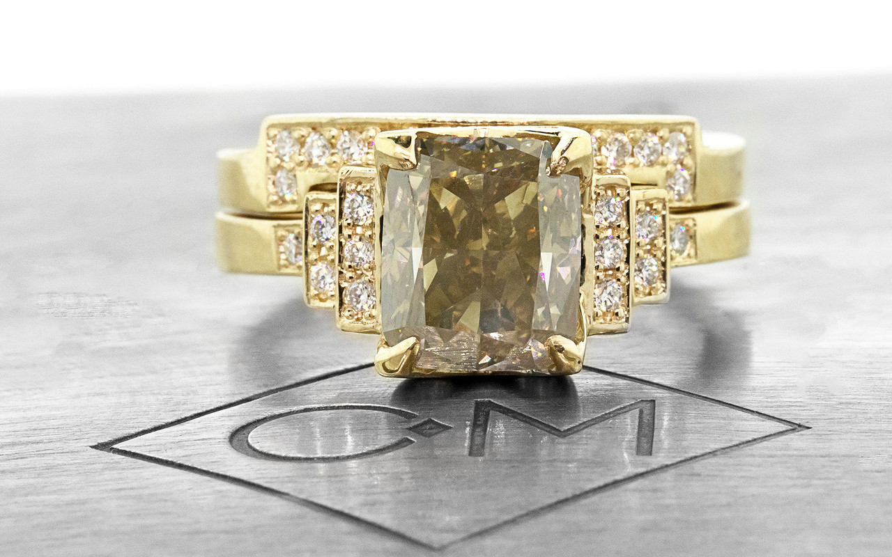 3.03 carat Champagne Diamond, emerald, rectangle cut engagement ring with shadow wedding band stacked with it.  Set is made in 14k recycled yellow gold.  White diamonds on the shoulders and in the weddings band.  Geometric design with art deco style.  Front view on metal plate with Chinchar/Maloney logo.