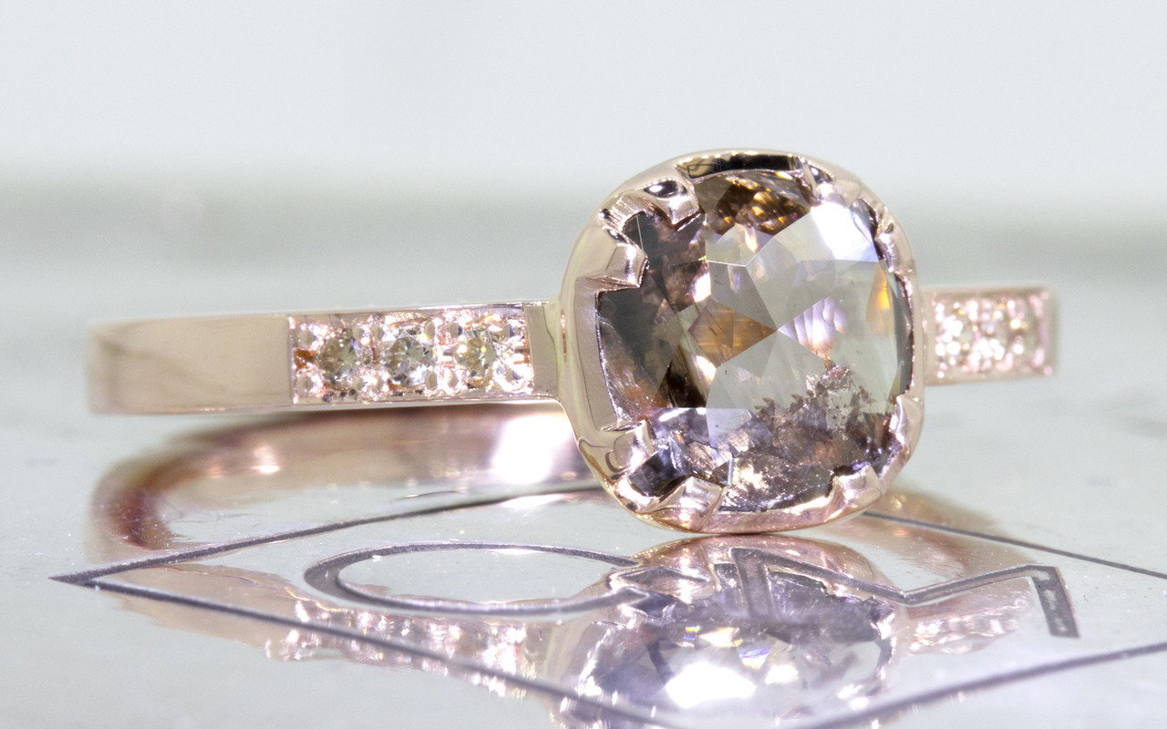 .84 carat cushion, rose cut translucent, smoky champagne prong/bezel set diamond ring with six 1.2mm brilliant champagne diamonds set into band set in 14k rose gold flat band. 3/4 view on metal background with Chinchar/Maloney logo
