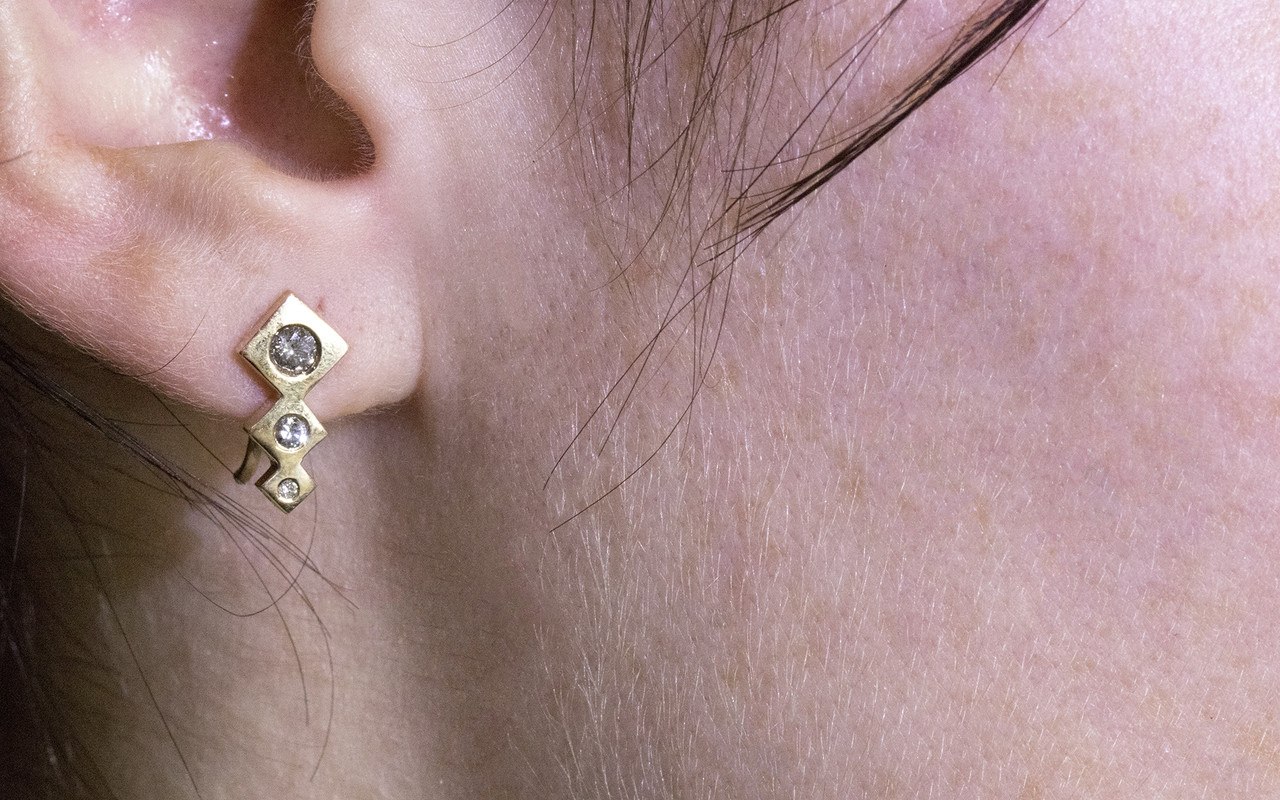 One earring modeled on an ear.  Earring is in dangle position.  Three square-diamond shapes in decreasing size make up the ear climber with brilliant, round gray diamonds are set into the earring also in decreasing size order.