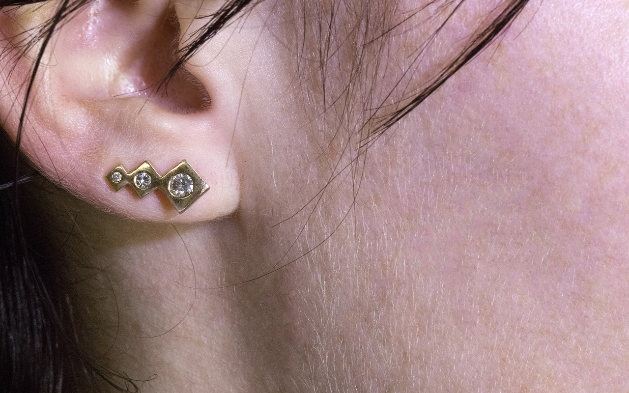 One earring modeled on an ear.  Earring is in ear climber position.  Three square-diamond shapes in decreasing size make up the ear climber with brilliant, round gray diamonds are set into the earring also in decreasing size order.