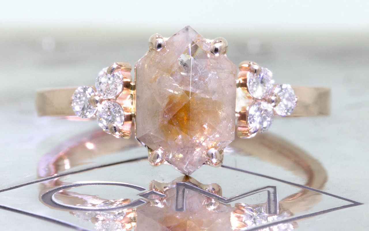 1.42 carat hexagonal, rose-cut gray and peach prong set diamond ring set in 14k rose gold with six 2mm brilliant white diamond clusters on either side of main setting flat band. Front view on metal background with Chinchar/Maloney logo